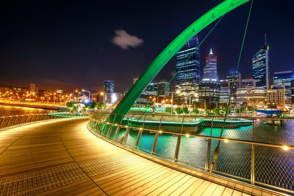 Wooden footpath of Elizabeth Quay Bridge illuminated by night at entrance of Elizabeth Quay marina, a new tourist attraction in Perth, Western Australia.Esplanade with modern skyscrapers on background